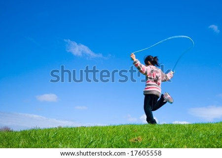 Young girl skipping on the green grass in the beautifull blue sky background - stock photo