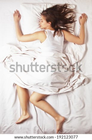 Young girl sleeping in bed on white sheets, shot from above - stock photo