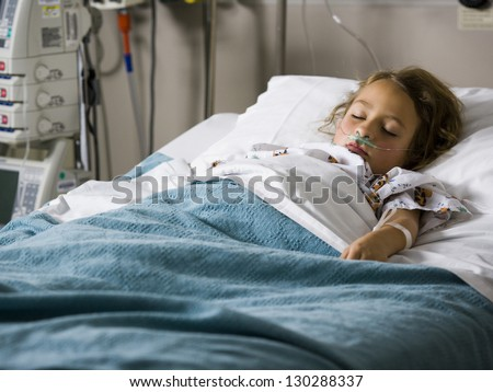 Young girl sleeping in hospital with oxygen tube - stock photo