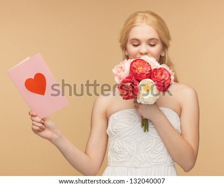 young girl smelling flowers and holding postcard - stock photo