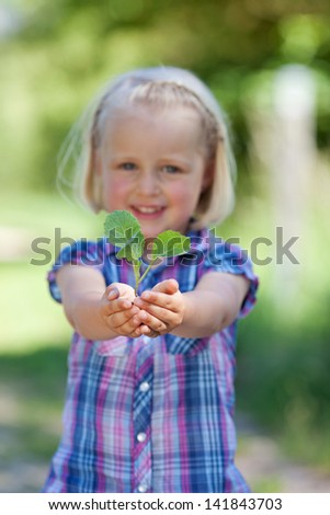 Young girl smiling and holding a little plant on her hands - stock photo