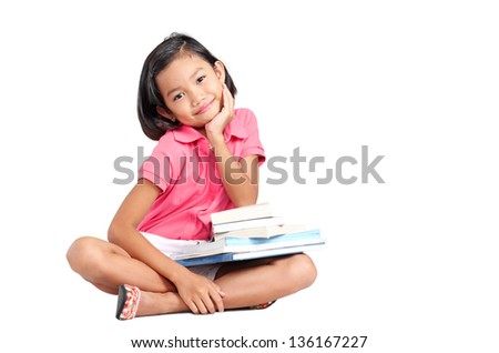 Young girl smiling and sitting on the floor with books on her lap. - stock photo