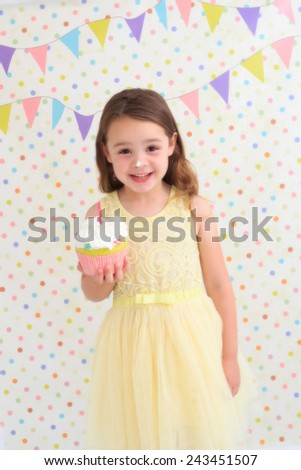 Young girl smiling, holding a birthday cake with cream on her nose - stock photo