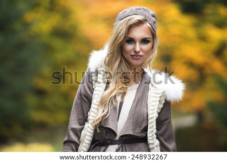 Young girl smiling in autumn scenery  - stock photo