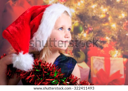 Young girl smiling wearing a santa hat - stock photo
