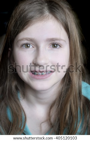 Young girl smiling with braces on her teeth - stock photo