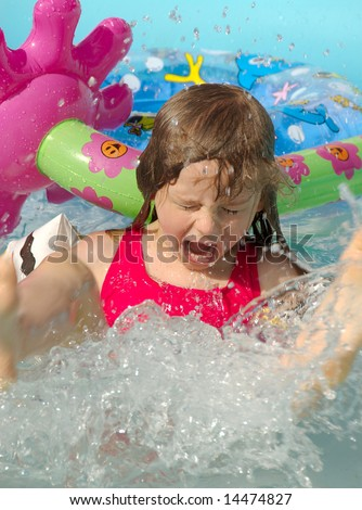 Young girl splashing in the pool - stock photo
