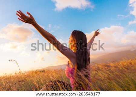 Young girl spreading hands with joy and inspiration facing the sun. - stock photo