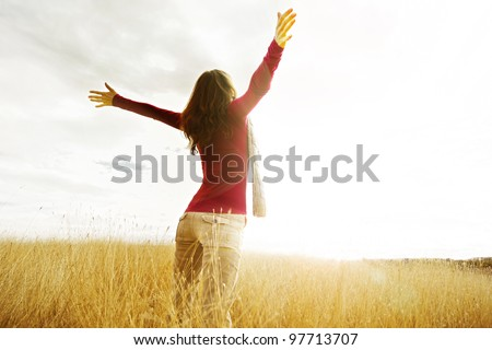 Young girl spreading hands with joy and inspiration facing the sun - stock photo
