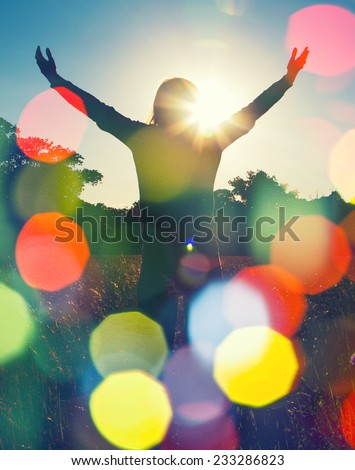 Young girl spreading hands with joy and inspiration facing the sun,sun greeting,freedom ,freedom concept - stock photo