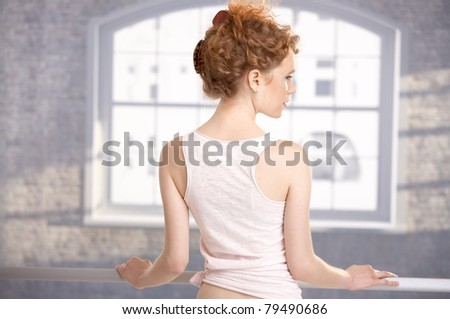 Young girl standing by bar in dance studio front of window showing her back.? - stock photo