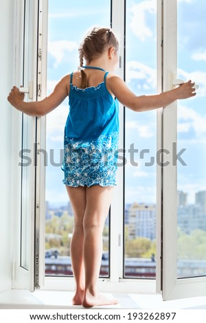 Young girl standing on window with opened door, looking from height - stock photo