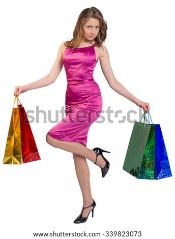 Young girl stands on one leg holding shopping bags. - stock photo