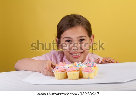 Young girl staring at a the camera with a bunch of cupcakes on a yellow background - stock photo