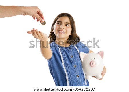 Young girl start her savings on a piggybank - stock photo