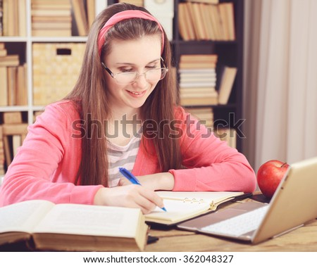 Young girl student sitting in the library and work at the table, the use of a laptop. - stock photo