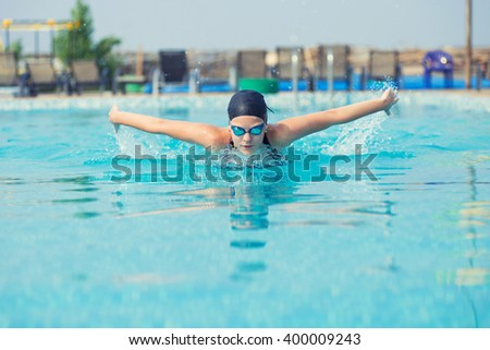 Young girl swimming butterfly stroke style - stock photo