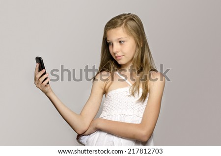 Young girl taking a selfie, kid taking a photo herself and having fun - stock photo