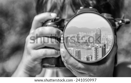 Young girl taking photos of Hong Kong skyline by professional digital camera. - stock photo