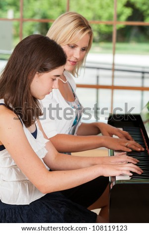 Young girl taking piano lessons from a teacher - stock photo