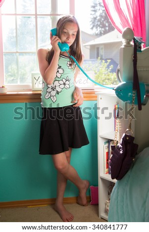 Young girl talking on the phone in her room - stock photo