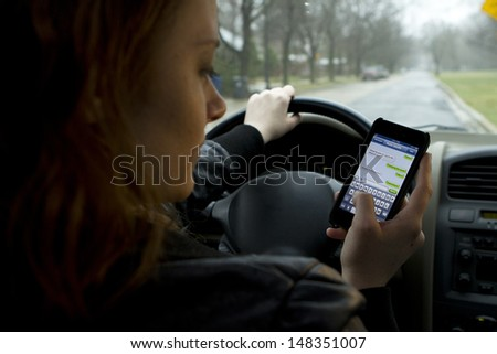 Young girl texting and driving, horizontal - stock photo