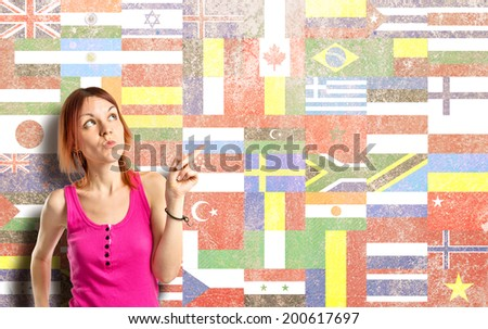 Young girl thinking over flags background  - stock photo