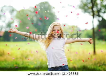 young girl throwing petals in the air - stock photo