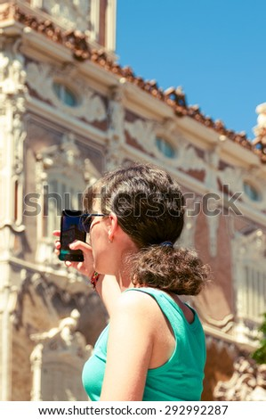 Young girl tourist  taking picture of historic building in Valencia, Spain - stock photo
