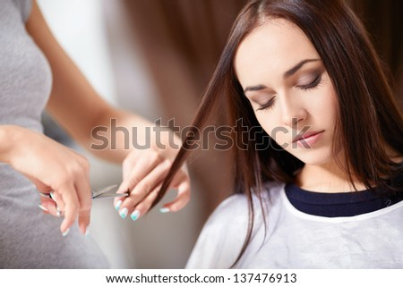 Young girl trimmed hair in a beauty salon - stock photo