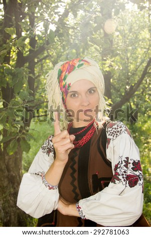 young girl, Ukrainian national costume, standing barefoot on the grass in the apple orchard - stock photo
