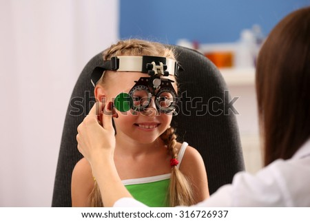 Young girl undergoing eye test with Spectacles on blurred background - stock photo