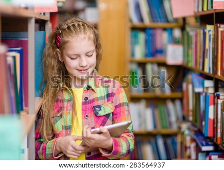 Young girl using a tablet computer in a library - stock photo