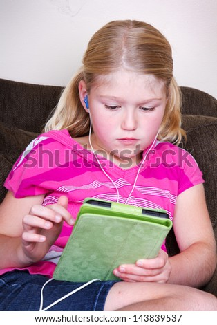 Young girl using a tablet with headphones sitting on couch - stock photo