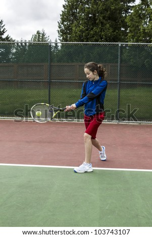 Young girl using a two handed backhand for lefthand tennis Player - stock photo
