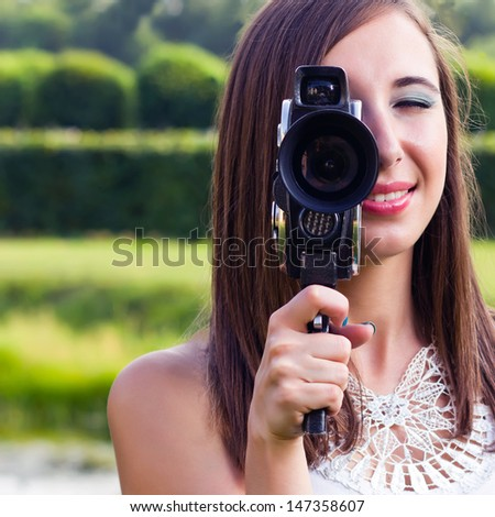 Young girl using an old fashioned cinema camera in a park - stock photo