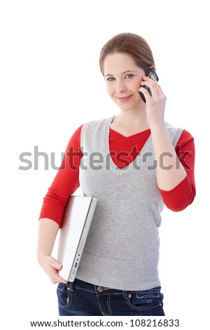 Young girl using mobile, holding laptop, smiling at camera. - stock photo
