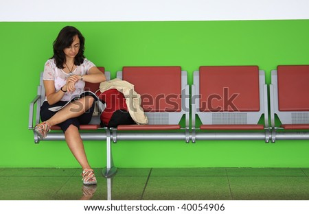 Young girl waiting on the airport bench - stock photo