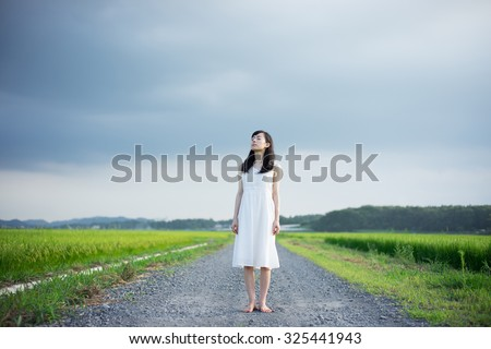 young girl walking down the country road - stock photo