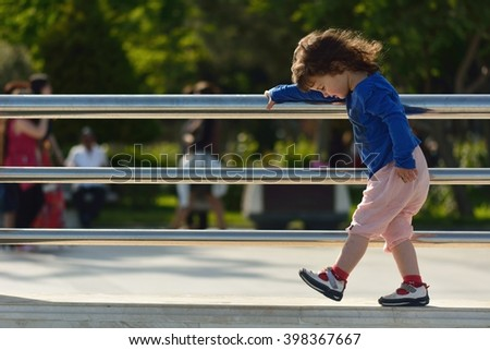 Young girl walking on wall holding metal railings. A small child taking careful steps on a wall, holding a railing and looking at her feet - stock photo