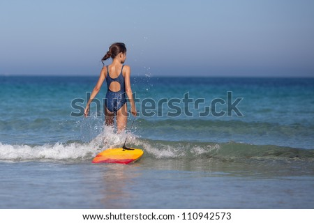 young girl walks with her surfboard in the sea - stock photo