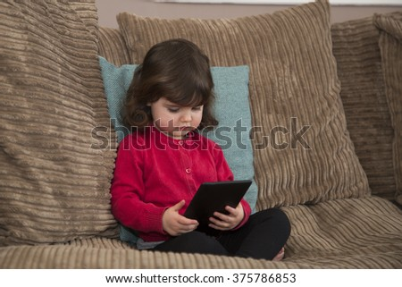Young girl watch cartoon on Tablet - stock photo