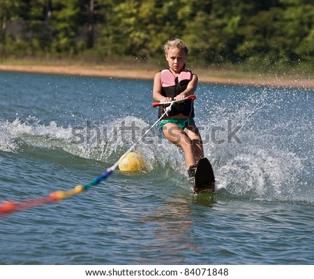 Young girl water skiing on a slalom course. - stock photo