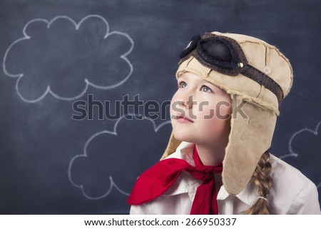 Young girl wearing aviator goggles and hat with chalk board and clouds in background - stock photo