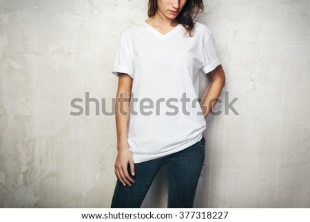 Young girl wearing blank t-shirt and black jeans. Concrete wall background - stock photo