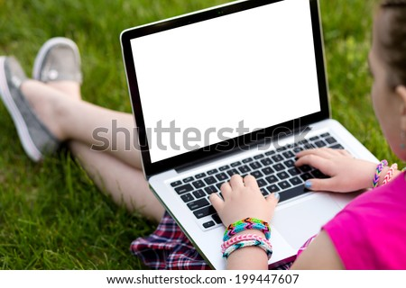 Young girl wearing loom rubber bracelets using the laptop, sitting on the grass in the park. Back to school, young fashion, life style concept - stock photo