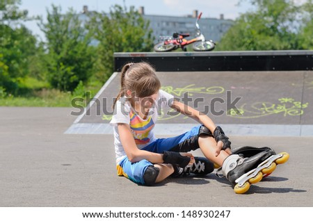 Young girl wearing rollerblades massaging her calf muscles as she sits on the ground at a skate park in front of a cement ramp - stock photo