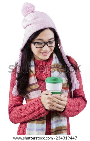 Young girl wearing winter jumper and holding hot coffee in a disposable cup at the studio - stock photo