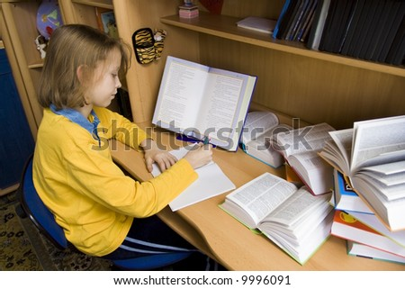 Young girl wearing yellow blouse sitting at the desk - stock photo