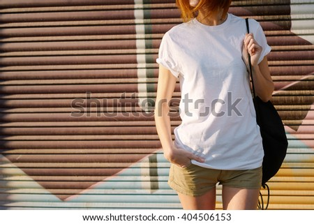young girl with a backpack wearing a white blank t-shirt standing on a graffiti wall background  - stock photo